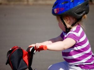 little girl wearing scooter helmet