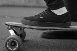 black skateboard shoes resting on top of skateboard