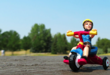 action figure of a kid riding a 3-wheeled bicycle