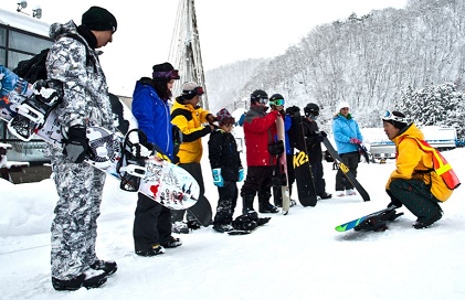 beginner snowboarders being taught by a senior snowboarder