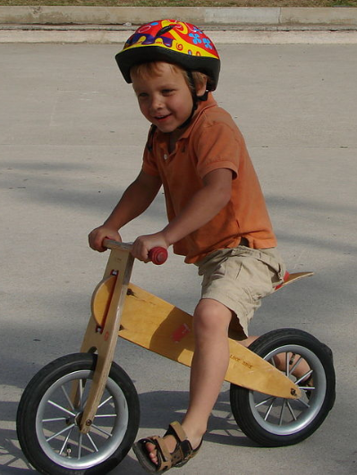boy riding his wooden balance bike