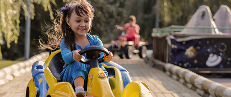 girl driving an electric car toy in safe track