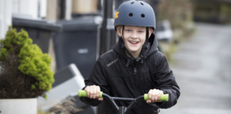 kid in a black jacket riding his black scooter