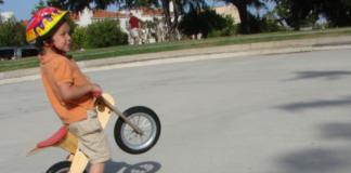 kid performing a mini wheelie on his balance bike