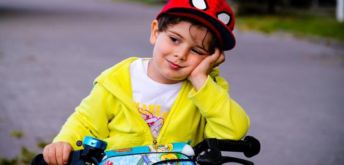 kid wearing yellow jacket smiling while riding a bike