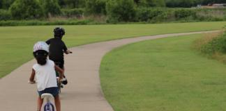 kids riding a bike following the concrete road
