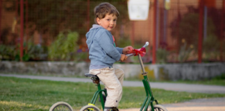 little boy riding his green 3-wheeled bike