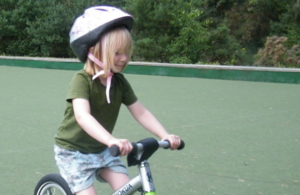 little girl riding her balance bike