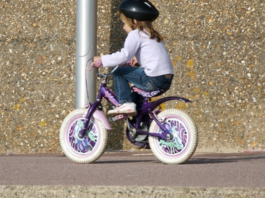 little girl wearing a helmet while riding a bike