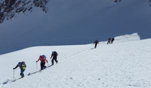 ski mountaineers hiking uphill path