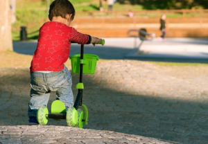 small boy riding his green scooter
