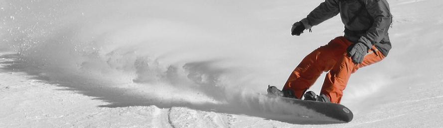 snowboarder turning hard on a downward slope