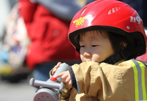 toddler wearing a red helmet tinkering a toy