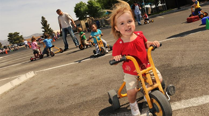 toddlers riding 3-wheeled bikes in the park