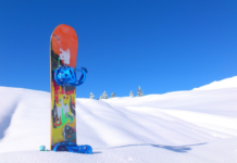 colorful snowboard erected in the snow