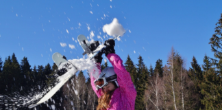 girl pink suit removing ice from snowboard