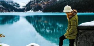 lady in green jacket snow lake mountain