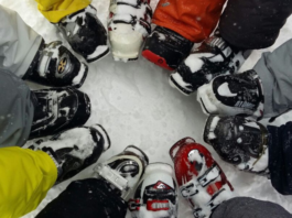 snowboarders showing their boots in a circle