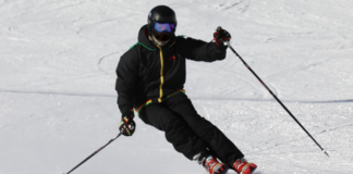 Man with black jacket and pants doing ski