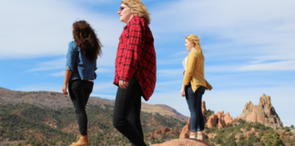 Three women standing over the hill