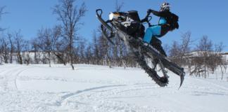 Man doing snowmobile stunt