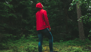 Man on the forest wearing red jacket