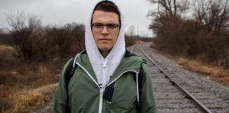 Man on the rail road wearing jacket