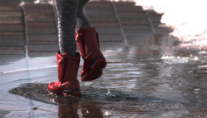 Person wearing red rain boots