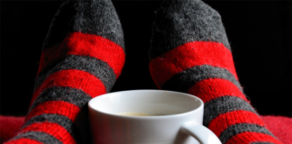 White mug in the middle of person's feet