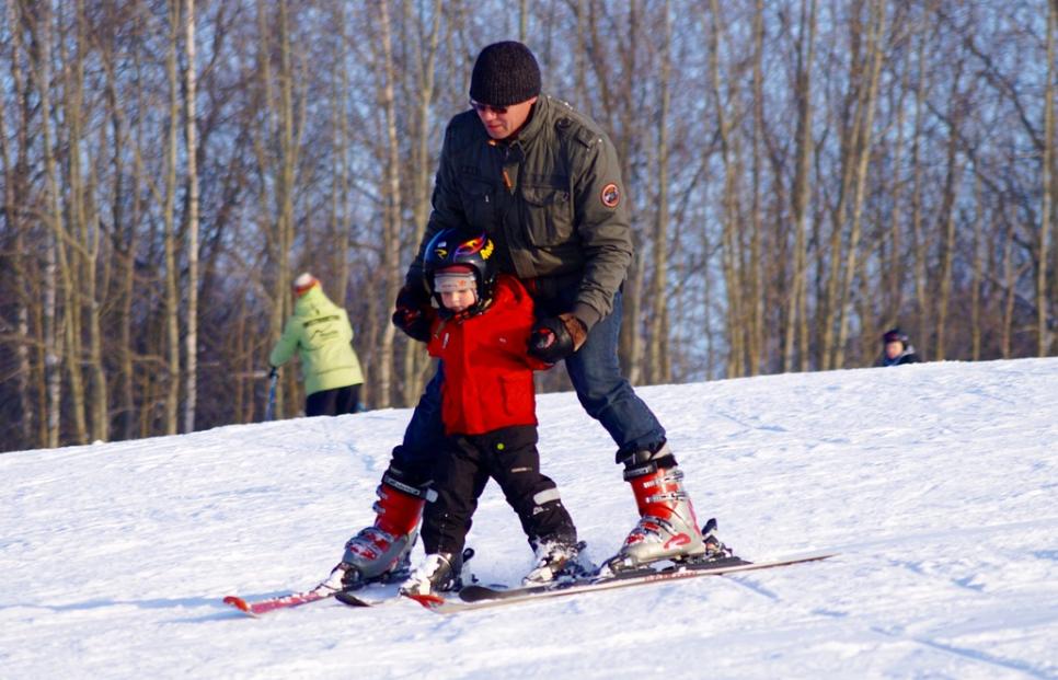 Man teaching a kid skiing