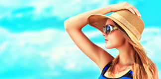 Happy young woman posing over blue sky
