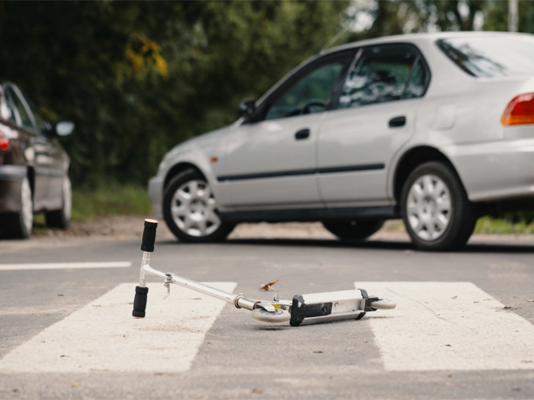 Scooter lying on a zebra crossing. Car crash concept