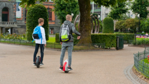 Two boys riding on a hoverboard