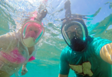 Young couple in full face masks for snorkeling making selfie under water