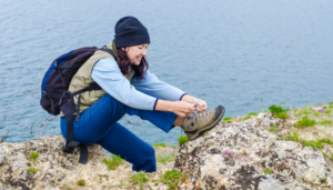 girl ties the laces on hiking boots