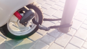 Combination security lock blocking the motor scooter wheel